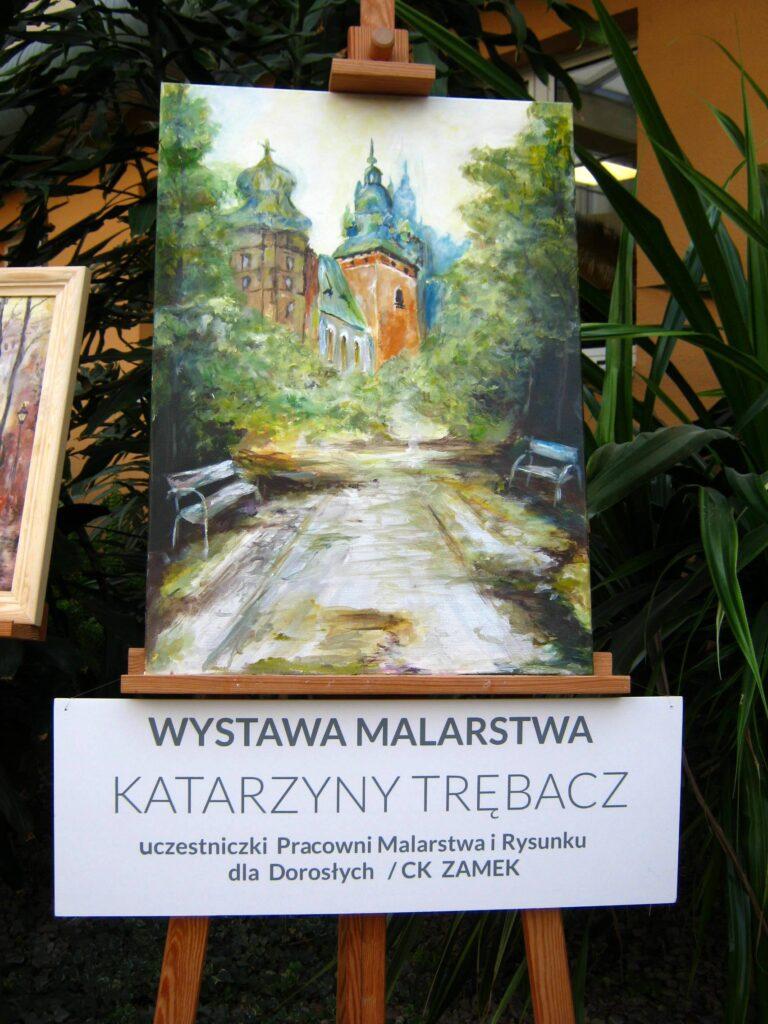 Wystawa malarstwa Katarzyny Trębacz – uczestniczki Pracowni Malarstwa i Rysunku dla Dorosłych CK ZAMEK. Na tle zieleni jeden obraz przedstawiający drogę prowadzącą do historycznej, znajdującej się w oddali, budowli.