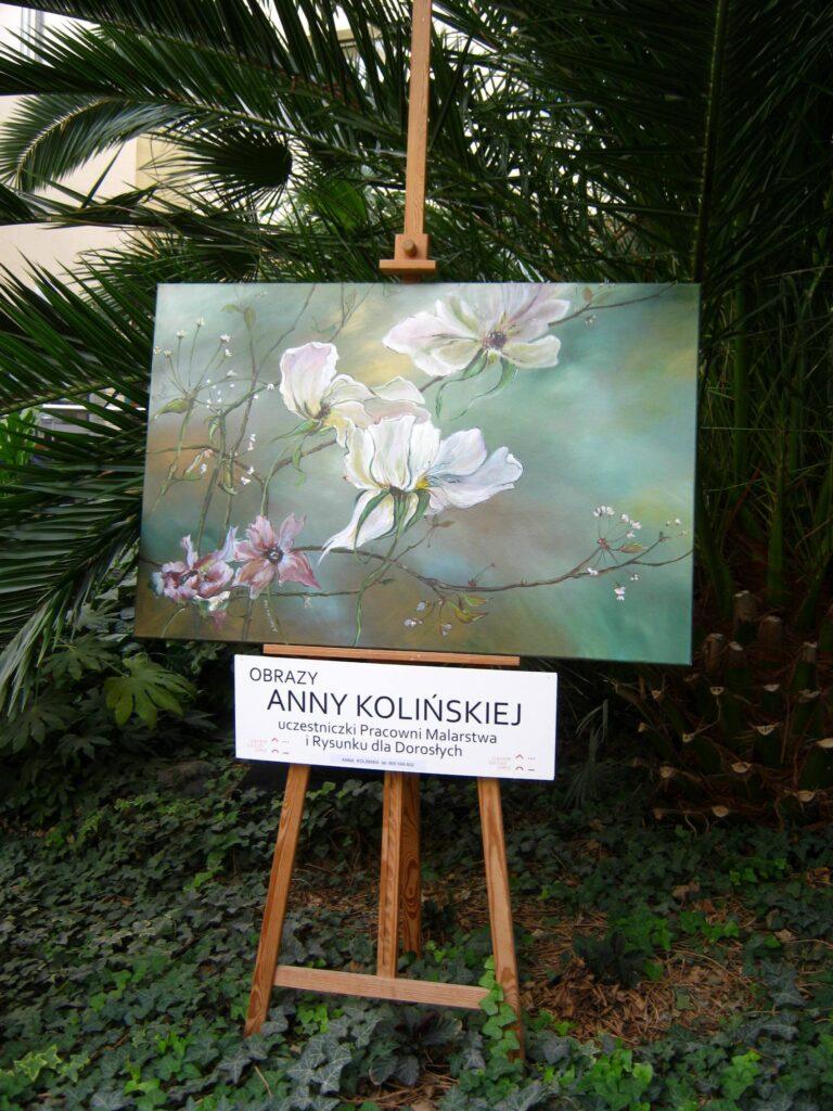 Obraz Anny Kolińskiej – uczestniczki Pracowni Malarstwa i Rysunku dla Dorosłych – stojący na sztaludze. W tle znajduje się Ogród Zimowy Wielkopolskiego Centrum Onkologii. Obraz przedstawia egzotyczne kwiaty.