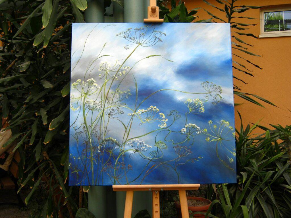 Obraz przedstawiający rośliny polne na tle błękitnego nieba, stojący na sztaludze w Ogrodzie Zimowym Wielkopolskiego Centrum Onkologii.