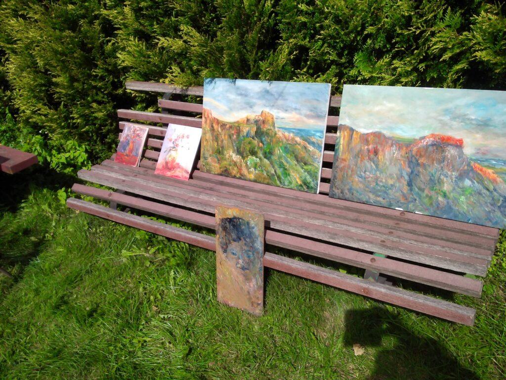 Ławka stojąca w ogrodzie, a na niej dwie duże prace przedstawiające strome zbocze wzniesień nad brzegiem morza oraz trzy małe prace. Niestety nie widać, co jest na nich namalowane.