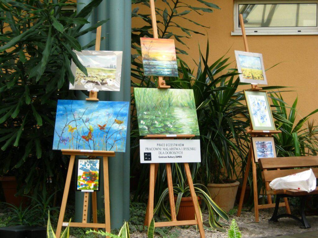 Na tle kwiatów doniczkowych wystawa ośmiu prac uczestników pracowni. Obrazy przedstawiają: motyle na gałęziach, szuwary i rośliny wodne, pejzaże.