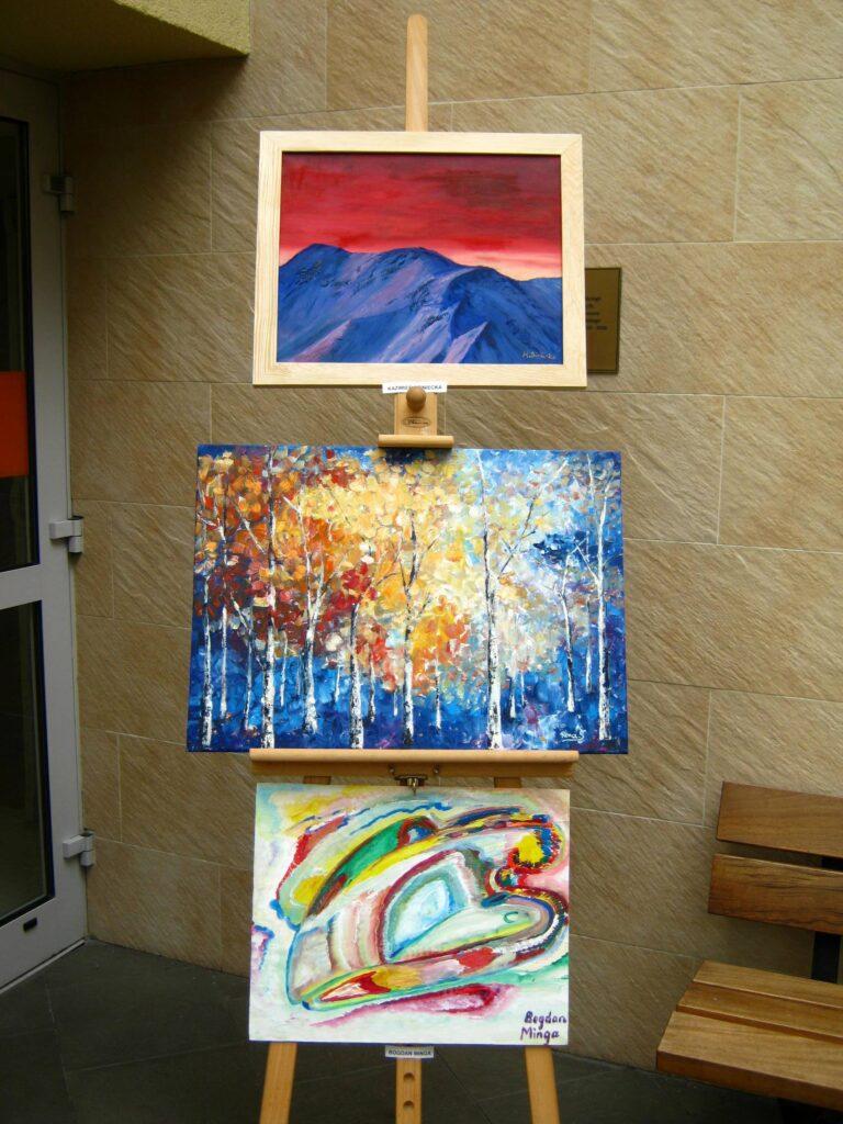 Na tle ściany trzy obrazy. Od góry: niebieskie wzgórza na tle czerwonego nieba, brzozy na niebieskim tle oraz kolorowa abstrakcja.