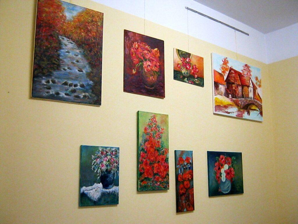 Na ścianie wisi osiem prac. Sześć przedstawia kwiaty w wazonie, jedna rzekę płynącą przez jesienny las, jedna stary młyn nad rzeczką.