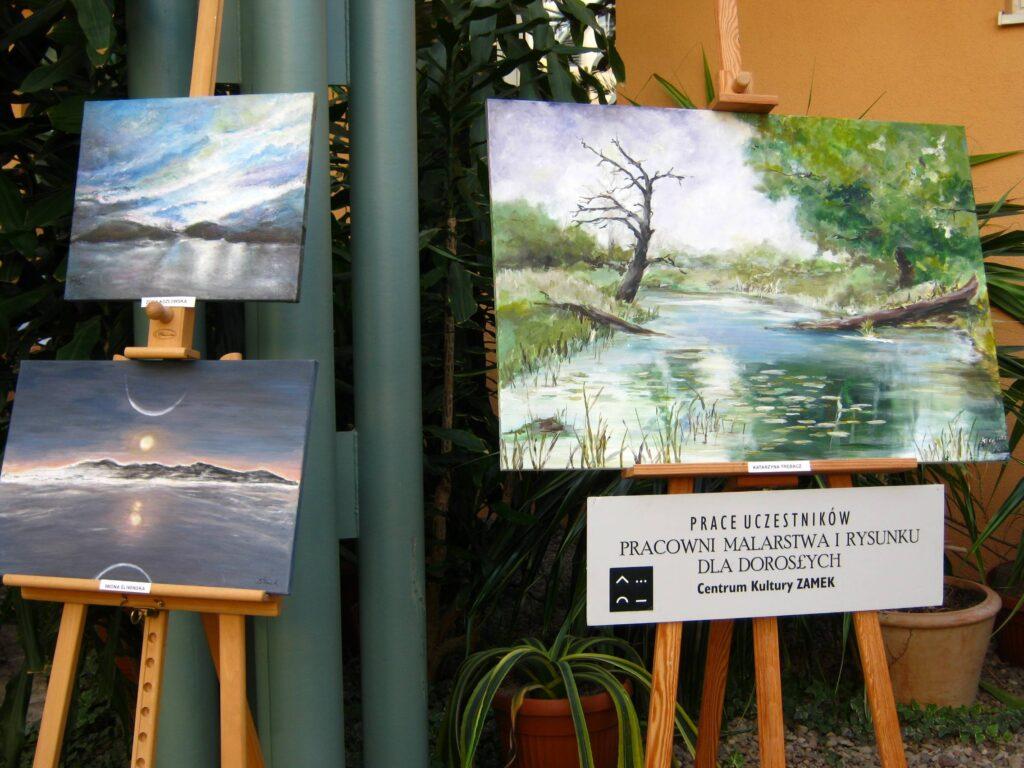 Wystawa obrazów uczestników pracowni w Wielkopolskim Centrum Onkologii. Trzy prace przedstawiające akweny wodne