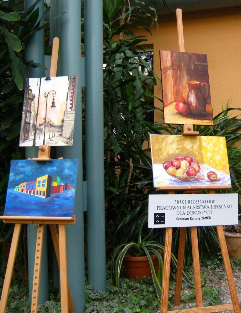 Wystawa prac uczestników pracowni w Wielkopolskim Centrum Onkologii. Cztery prace przedstawiają: zabytkowe latarnie stojące przy ulicy, modernistyczne budynki, dzban i jabłko, misa z jabłkami.