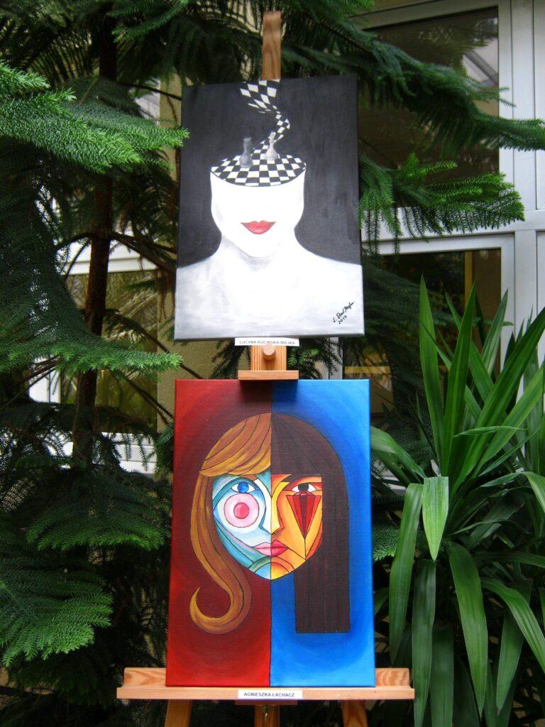Na tle drzewa iglastego stoją dwie prace oparte o sztalugę. Przedstawiają twarz kobiety w stylu surrealizmu.