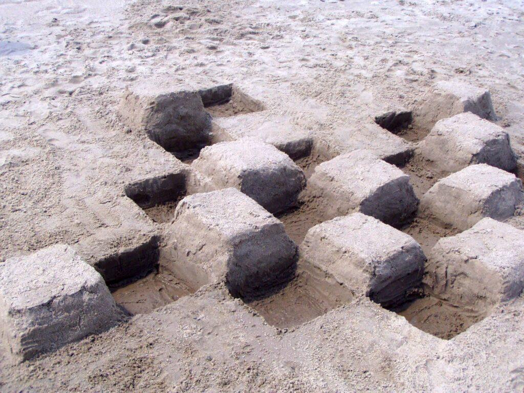Rzeźba z piasku na plaży, przedstawiająca sześciany ułożone w szachownicę.