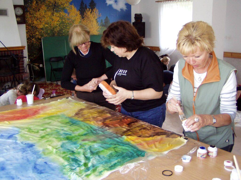 W świetlicy trzy kobiety pochylone nad jedną, dużą, rozłożoną na stole pracą. Malują coś na dużej tkaninie.