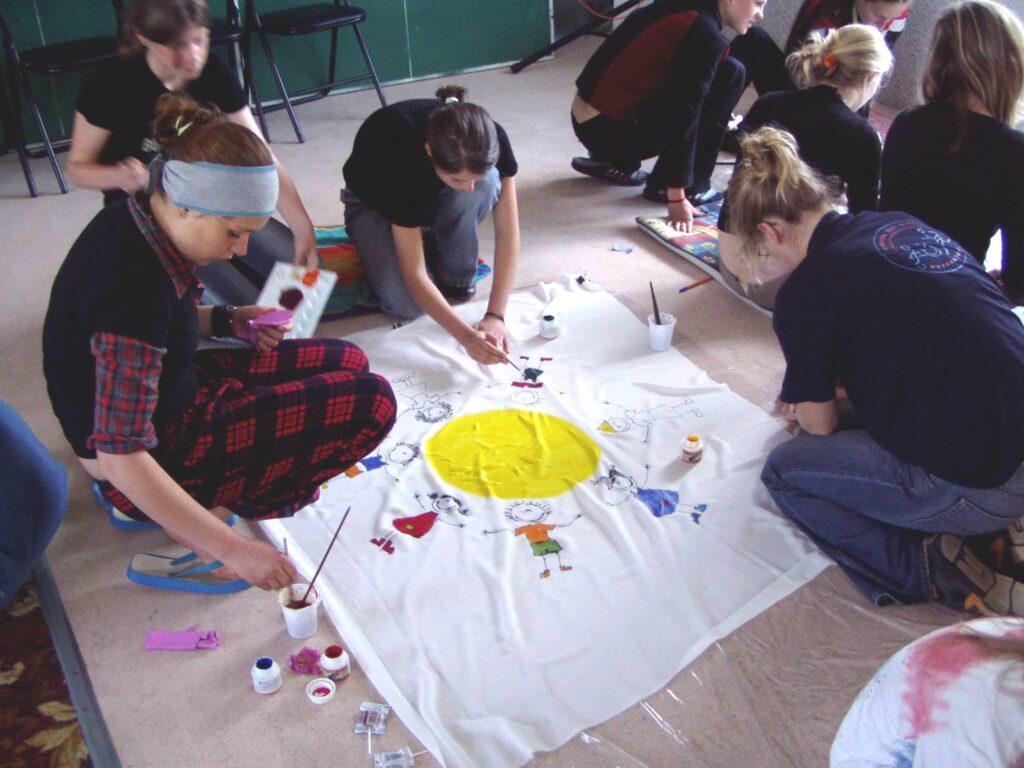 W sali na podłodze rozłożone jest duże płótno. Cztery klęczące przy tkaninie dziewczyny malują na niej słońce, wokół którego, w kręgu, stoją dzieci.
