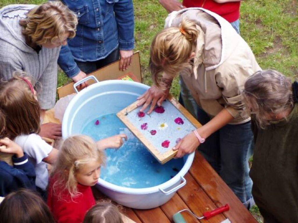 W ogrodzie na stole stoi duża misa z wodą. Wokół stoją dzieci i trzy kobiety, jedna z nich trzyma w rękach pracę wykonaną z papieru czerpanego, ozdobionego naturalnymi kwiatami.