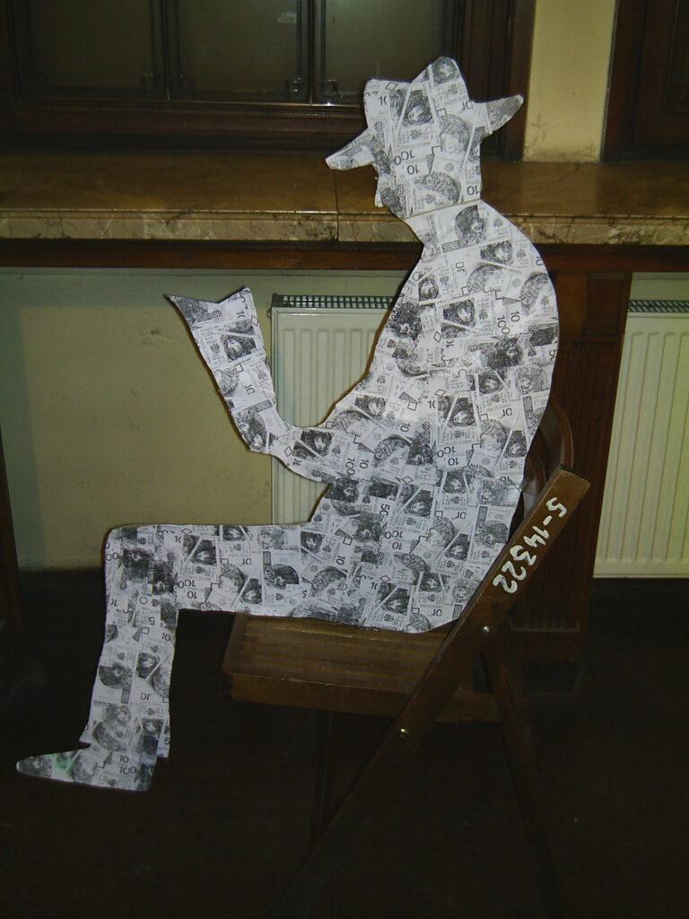 Instalacja przestrzenna – płaska, pokryta banknotami sylwetka siedzącego na drewnianym krześle mężczyzny.