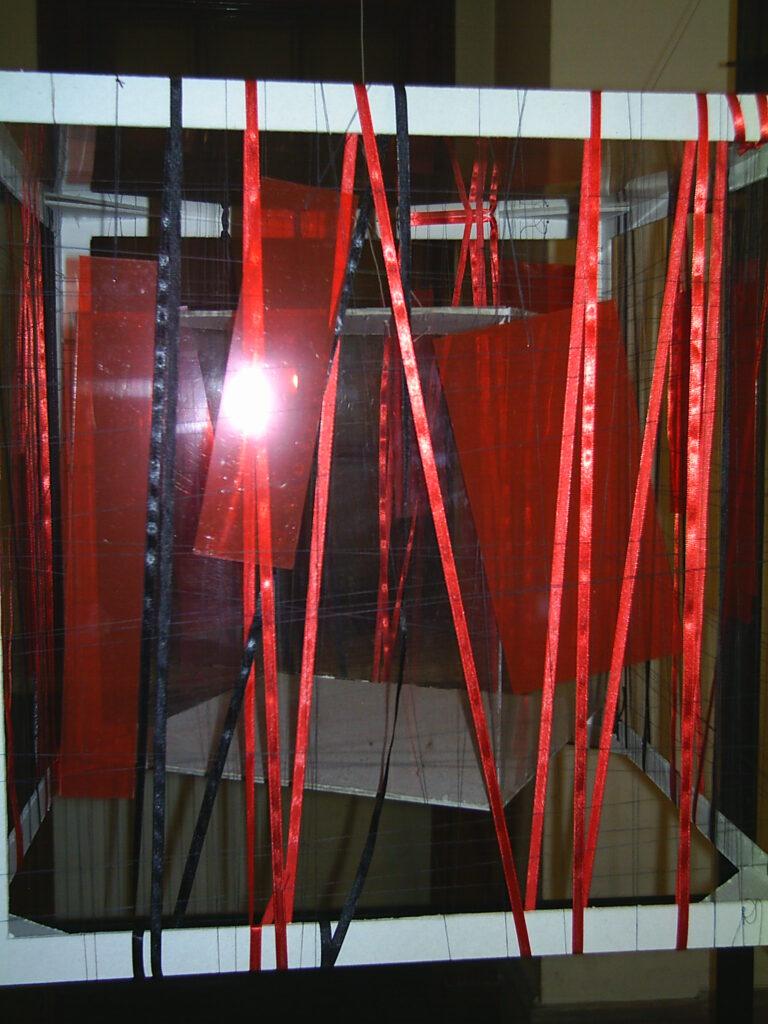 Przestrzenna instalacja – w białym szkielecie sześcianu znajdują się czerwone kawałki przejrzystego plastiku, boki wykonane z czerwonej i czarnej tasiemki.