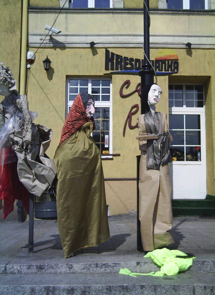 Performance na placu miejskim – trzy kukły o wymiarach człowieka stoją przy latarni. Wykonane są z gipsu, tkanin, papieru i drutu.
