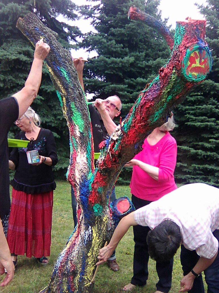 Grupa dorosłych uczestników maluje stojący w ogrodzie, dwu i półmetrowy pień ściętego na tej wysokości drzewa.