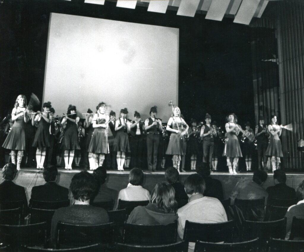Czarno-biała fotografia przedstawiająca scenę Sali Wielkiej, na której występuje grupa tancerek. Na pierwszym planie publiczność siedząca na krzesłach.