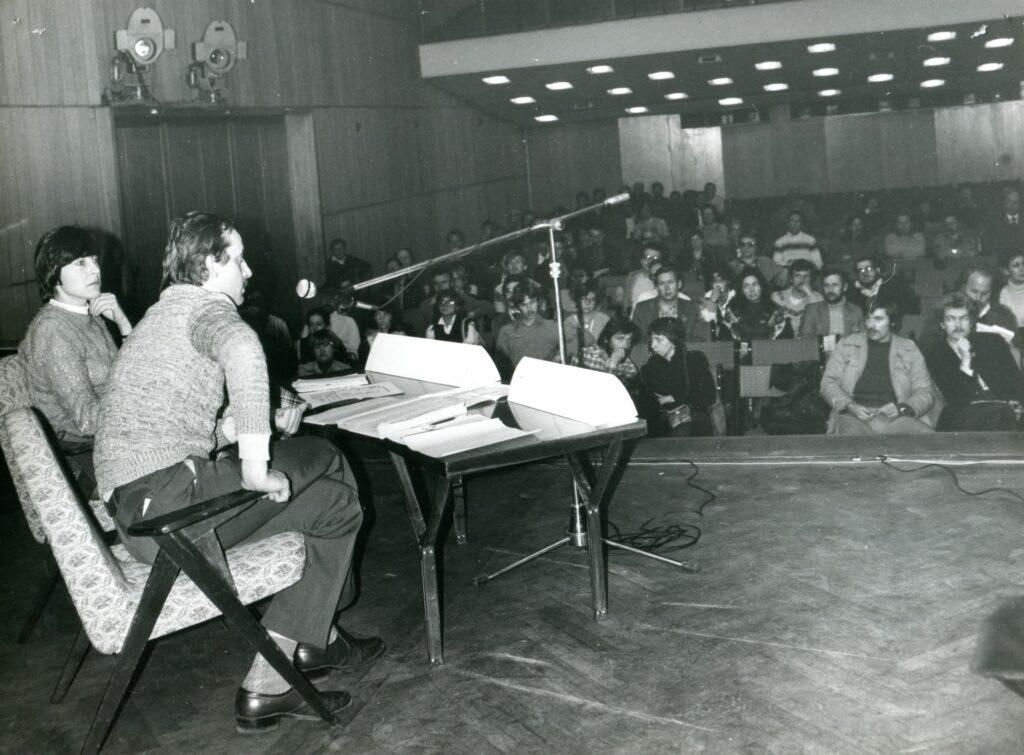 Na archiwalnej fotografii widać wnętrze dawnej Sali Wielkiej. Po lewej stronie widać kobietę i mężczyznę, siedzących na typowych fotelach z okresu PRL-u, mężczyzna mói do mikrofonu na statywie, na stole stos kartek. W tle publiczność.