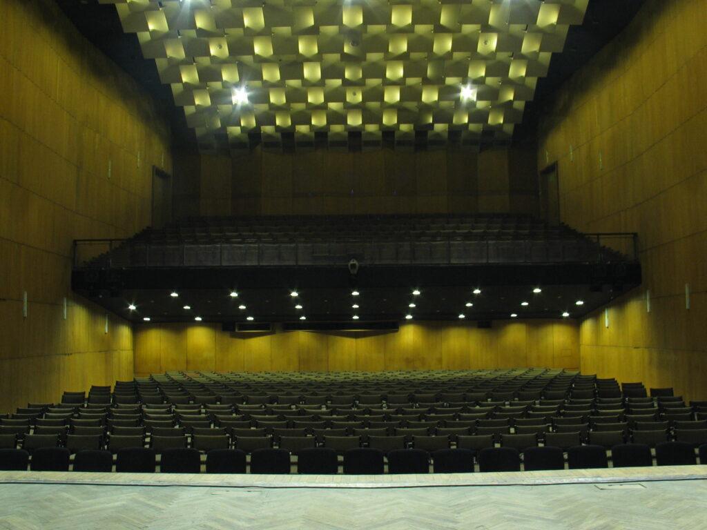 Fotografia archiwalna w żółtej barwie przedstawia Salę Wielką z perspektywy sceny - rzędy czarnych foteli podświetlonych lampami na parterze oraz lożę.