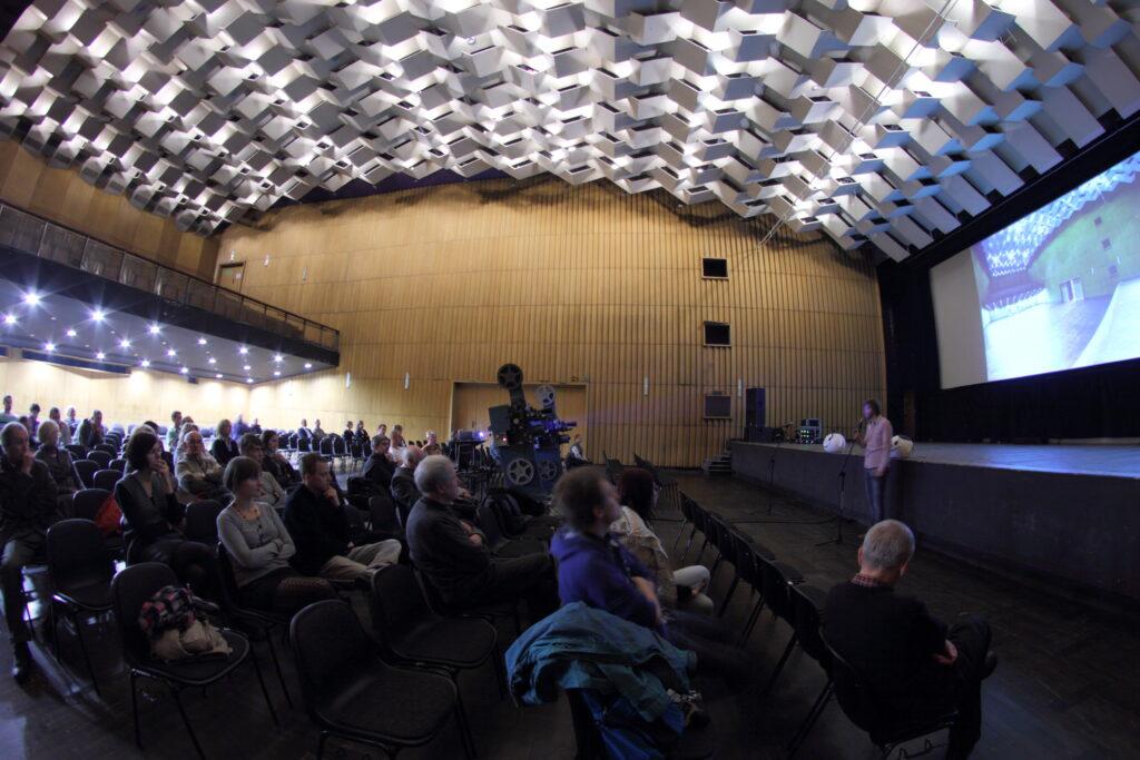 Sala Wielka widziana z prawej strony. Na pojedynczych krzesłach siedzą widzowie wpatrzeni w scenę, przed którą przemawia prelegent. Na ekranie kinowym zdjęcie sali. Ściana w tle wyłożona drewnianą boazerią.