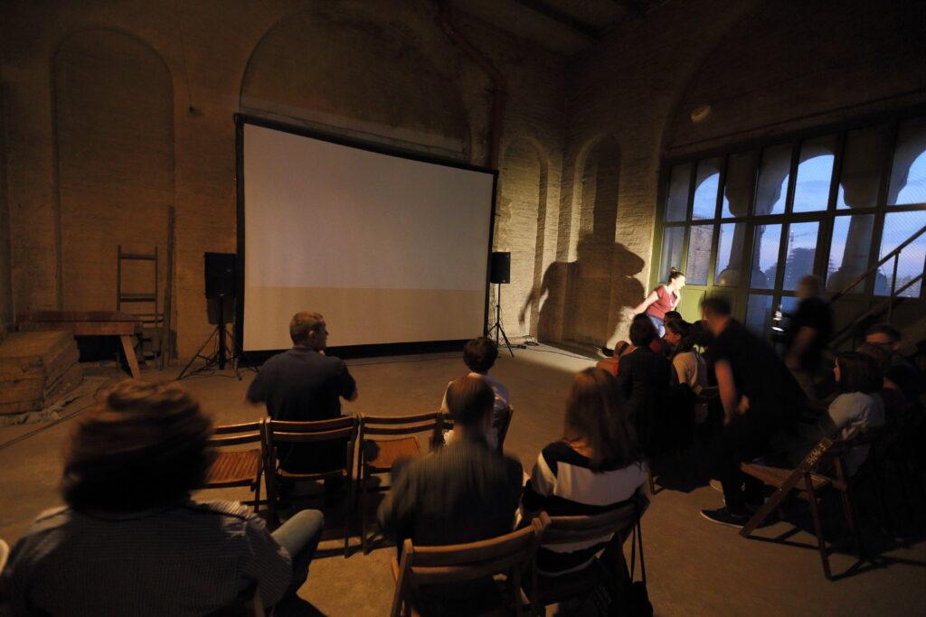 Zdjęcie przedstawia grupę ludzi w ciemnym pomieszczeniu. Siedzą na drewnianych, rozkładanych krzesłach przed przenośnym ekranem. Ściany pomieszczenia są gołe, widać zarysy szarych cegieł. We wnęce na lewo stoi sztaluga, drewniany stół, na dywanie obok lezą materace. Za dużym oknem wychodzącym na budujący się Bałtyk zapada zmrok.