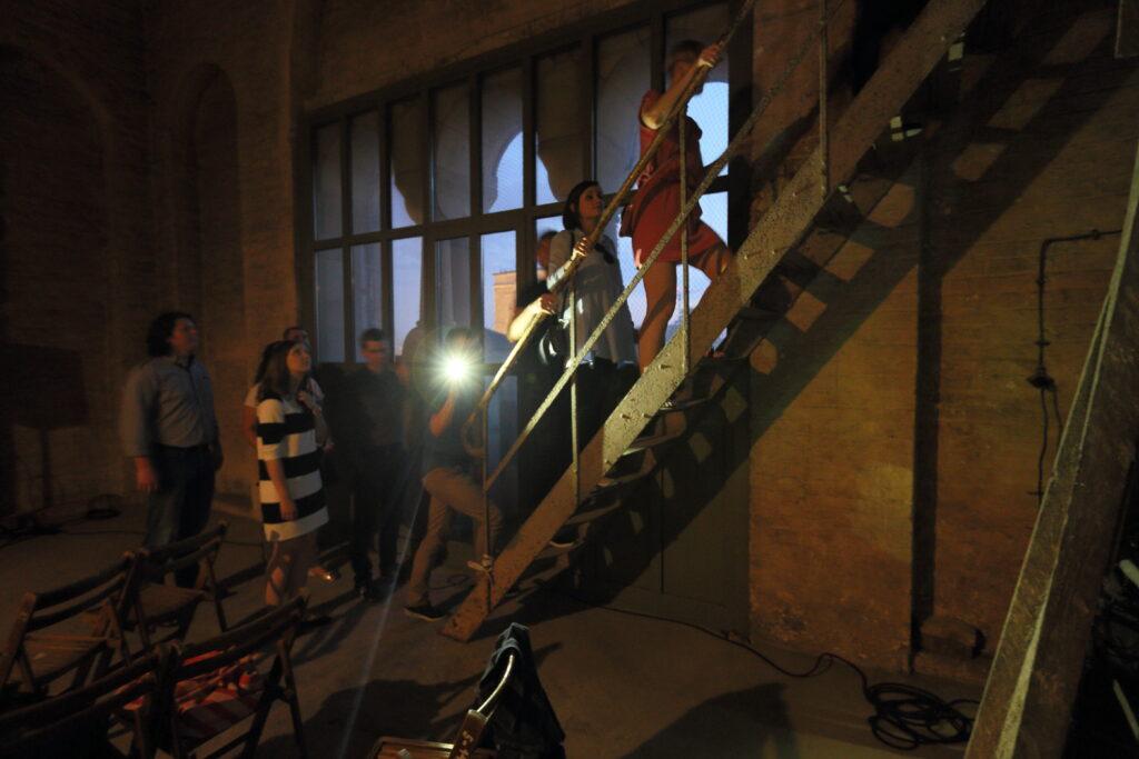 Zdjęcie przedstawia ciemne pomieszczenie. Grupka ludzi wspina się po metalowych schodach. Jedna z osób świeci latarką w stronę obiektywu. Z boku stoją drewniane, rozkładane krzesła. Za dużym oknem wychodzącym na budujący się Bałtyk zapada zmrok.