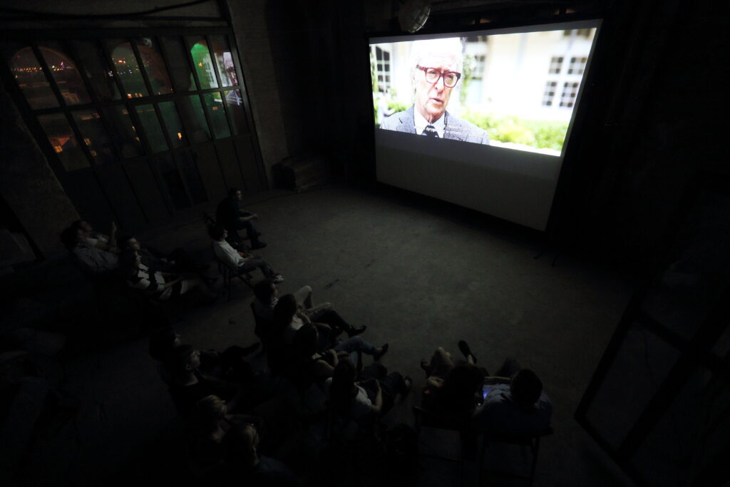 """Duże, ciemne pomieszczenie, betonowa podłoga. Grupka widzów siedzi na krzesłach dookoła przenośnego ekranu. Na ekranie Michael Caine w filmie """"Młodość"""".  Za dużym oknem mrok rozświetlany światłami miasta."""