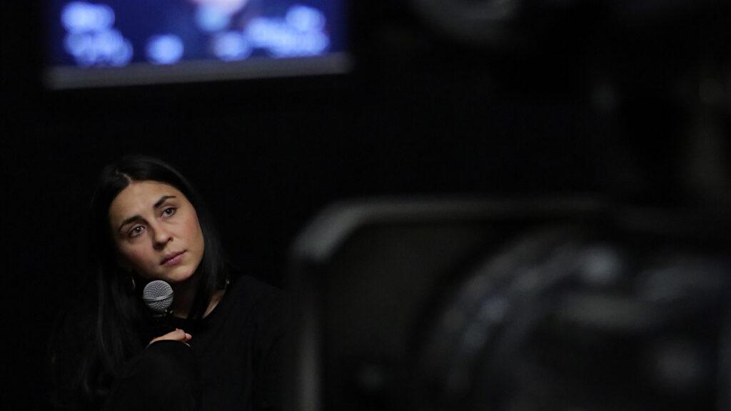 Zdjęcie robione zza kamery. Widać kawałek ekranu z podglądem obrazu. Przed kamerą spoglądająca w przestrzeń (na widownię?) kobieta, trzymająca mikrofon. To Jagoda Szelc.