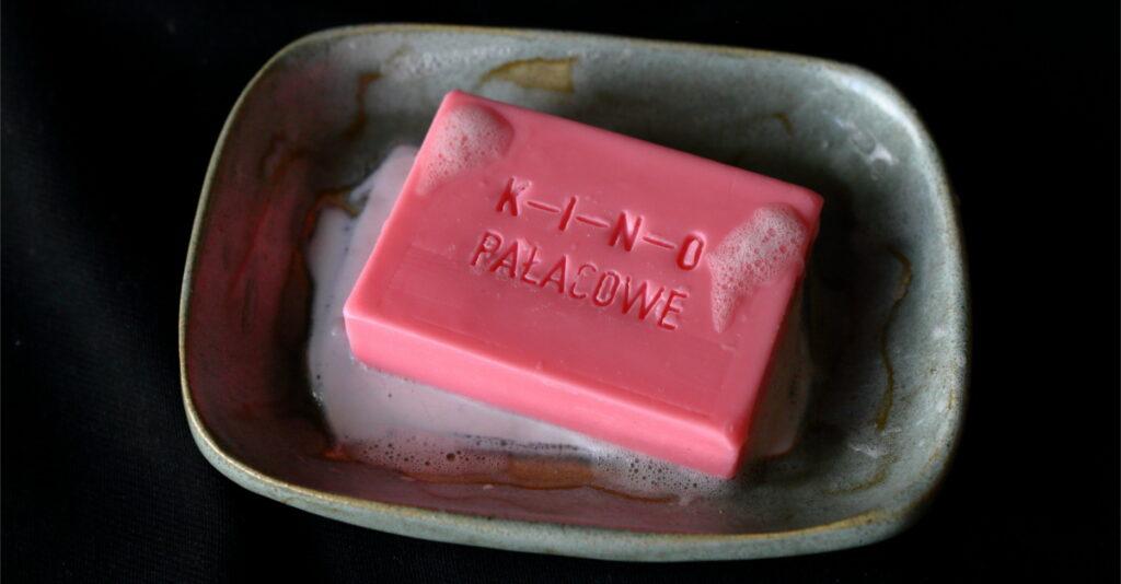 """Zdjęcie przedstawia różowe mydło z napisem """"Kino Pałacowe"""" leżące na podstawce. Na mydle i w jego okolicach widoczna jest piana."""