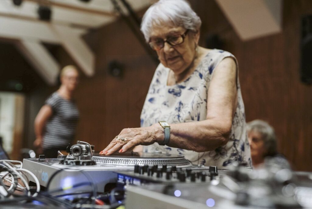 Starsza kobieta stoi lekko pochylona nad stołem, na którym ustawiona jest konsoleta do miksowania muzyki. Lewą dłonią dotyka płyty winylowej. Pani Zofia ma na nosie okulary w czerwonych oprawkach. Jej paznokcie pomalowane są w kolorze komponującym się z oprawkami. Na nadgarstku widoczny jest srebrny zegarek.
