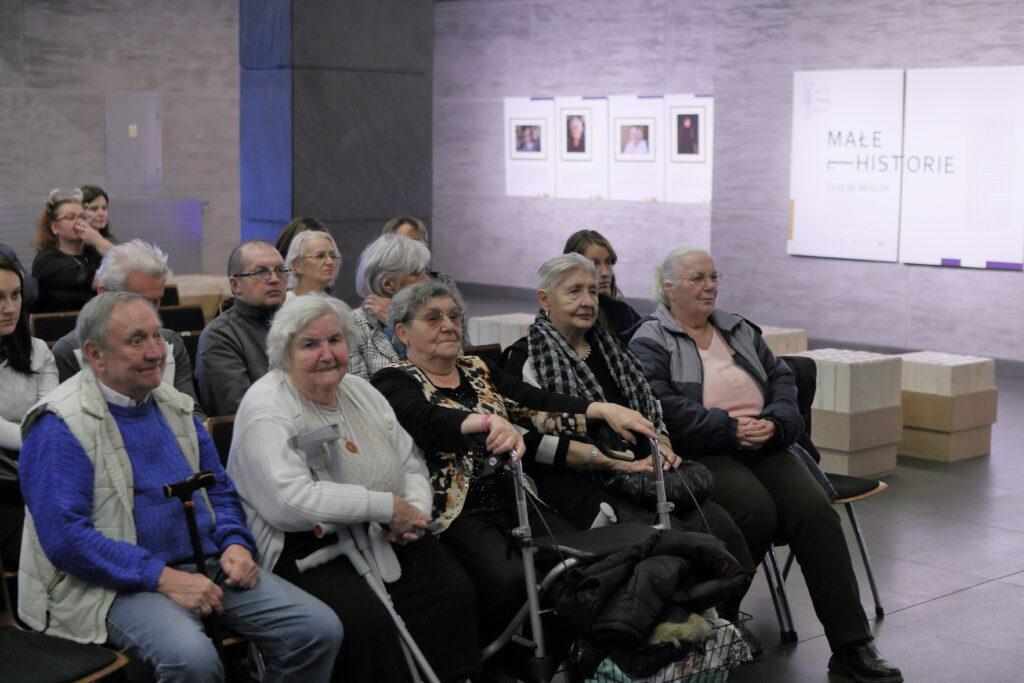 """Kilkunastoosobowa grupa – w większości starszych osób – siedzi na krzesłach rozstawionych w Holu Wielkim w Centrum Kultury ZAMEK. Niektórzy siwowłosi seniorzy i seniorki trzymają przed sobą laski lub kule ortopedyczne. Wszyscy wyglądają na wsłuchujących się w opowieść osoby, która nie zmieściła się w kadrze. To otwarcie wystawy """"Małe historie"""". Na ścianach w oddali widać zawieszone fotografie i tablice informacyjne."""