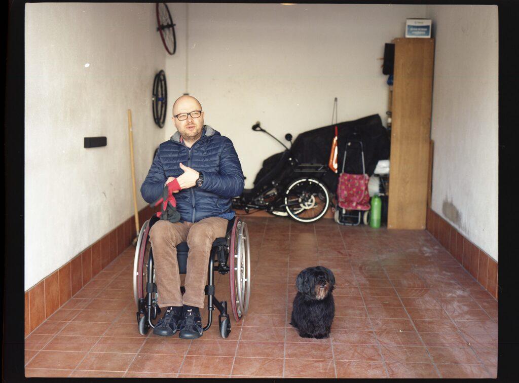 Bezwłosy mężczyzna w średnim wieku i w okularach, ubrany w granatową zimową kurtkę, brązowe sztruksy i czarne adidasy siedzi na wózku. Spogląda w naszą stronę – prawdopodobnie mówi coś do fotografa. Nie przeszkadza mu to by w tym samym czasie zakładać rękawiczki. Po jego lewej stronie przycupnął długowłosy, czarny pies. To pomieszczenie to najpewniej garaż – w tle można dostrzec wiele nieużywanych już przedmiotów.