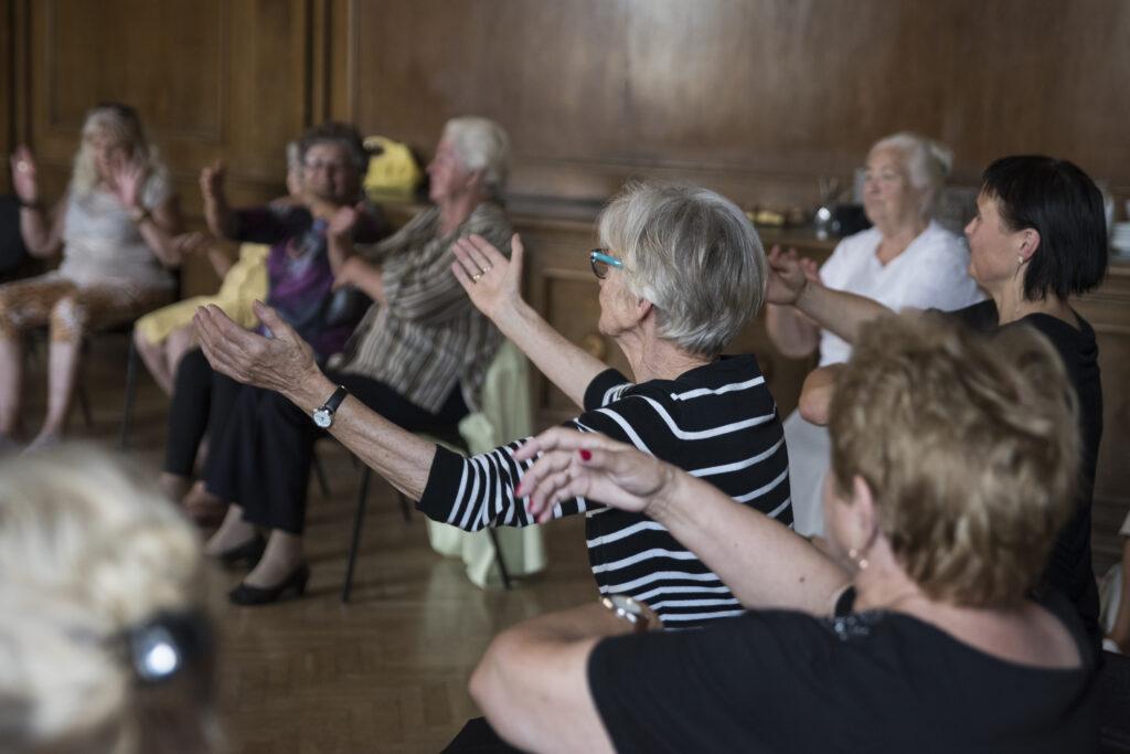 Kilkuosobowa grupa kobiet – w większości seniorek – siedzi w okręgu. Fotografka ujęła je stojąc za ich plecami. Panie mają uniesione do góry ręce – wykonują nimi różne ruchy. To performatywne warsztaty prowadzone przez aktorkę Barbarę Prądzyńską,