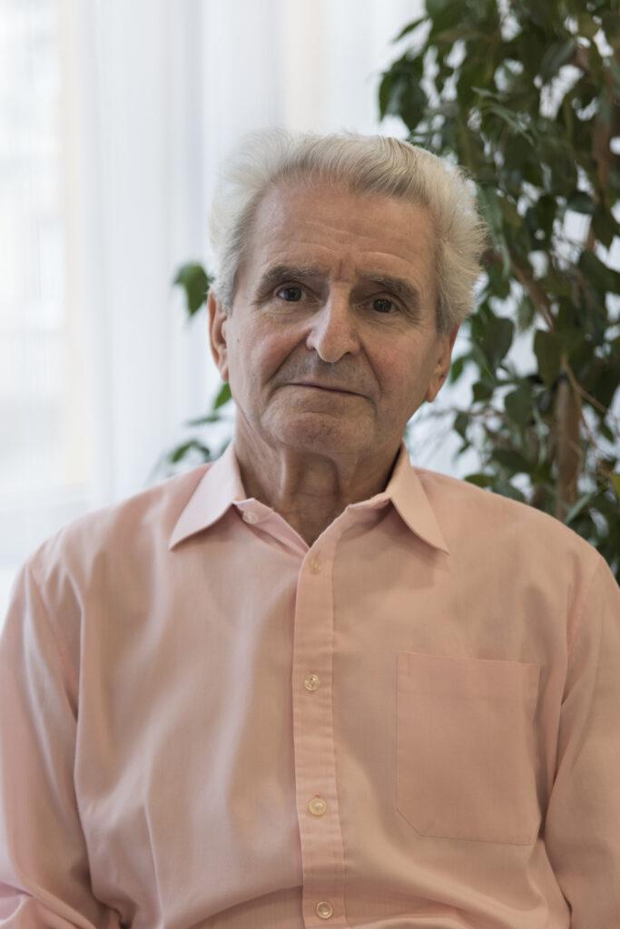Starszy, siwowłosy mężczyzna stoi wyprostowany. Spogląda prosto w obiektyw fotografki. Jest ubrany w różowawą koszulę z kołnierzykiem zapinaną na guziki. Za jego plecami, po prawej stronie można dostrzec zielone liście – prawdopodobnie to liście doniczkowego kwiatu.