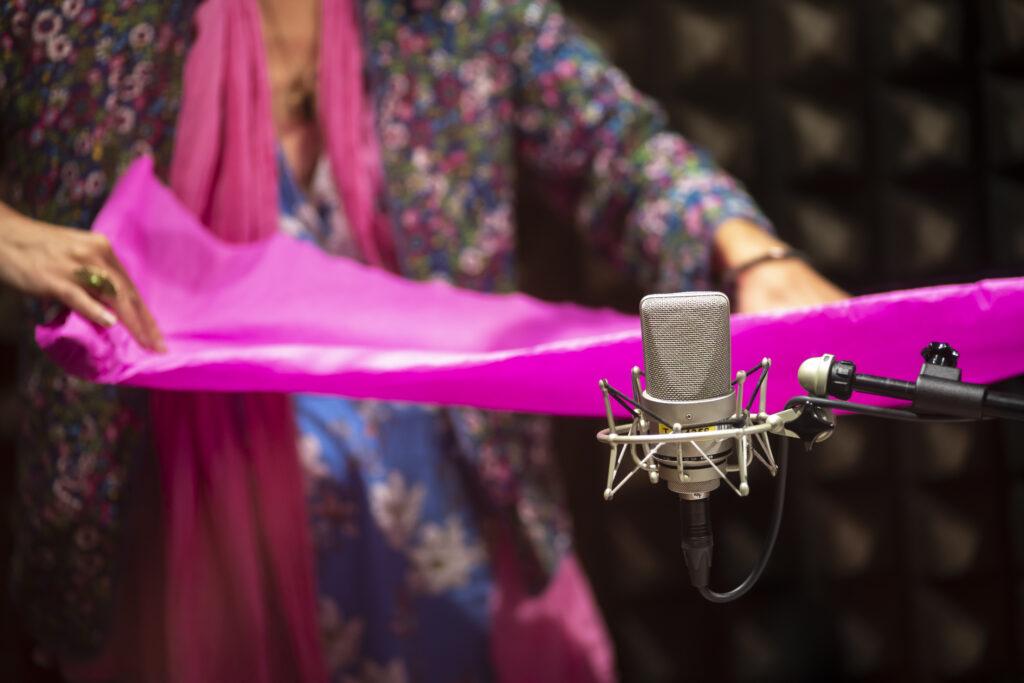 Na pierwszym planie jest radiowy mikrofon. Na drugim uwieczniono korpus kobiety trzymającej pomarszczoną bibuły. Materiał jest koloru różowego. Postać ubrana jest w wielokolorową tkaninę. Na palcach prawej dłoni ma założony pierścień.