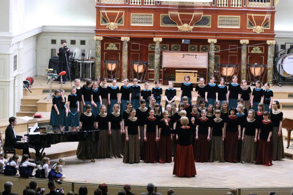 Na scenie w Auli UAM stoi chór kilkudziesięciu dziewcząt. Przed nimi, tyłem, stoi kobieta wykonująca gest dyrygenta. Zarówno dziewczęta, jak i kobieta ubrane są w spódnice do ziemi o różnych kolorach i czarne bluzki z pluszu z krótkimi rękawami oraz kryzami w kolorze spódnic. W tle znajdują się organy, po lewej stronie fortepian i siedzący przy nim pianista. Na dole, po lewej stronie siedzą na scenie małe dziewczynki w jednakowych biało-niebieskich kostiumach. Fotografia została wykonana tuż przed rozpoczęciem kolejnego utworu.