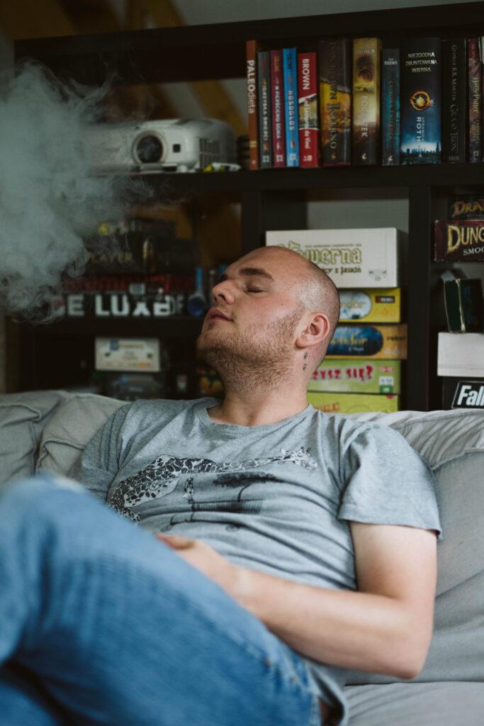 """Młody mężczyzna """"przed trzydziestką"""", z ogoloną głową siedzi na kanapie w swoim pokoju. Jest ubrany w szarą koszulkę i niebieskie dżinsy. Ma lekko odchyloną do tyłu głowę. Jego twarz zwrócona jest w prawą stronę – z ust wydobywa się wydmuchiwany dym. Szymon ma przymknięte powieki. Za jego plecami jest półka, na której ustawione są głównie gry planszowe."""
