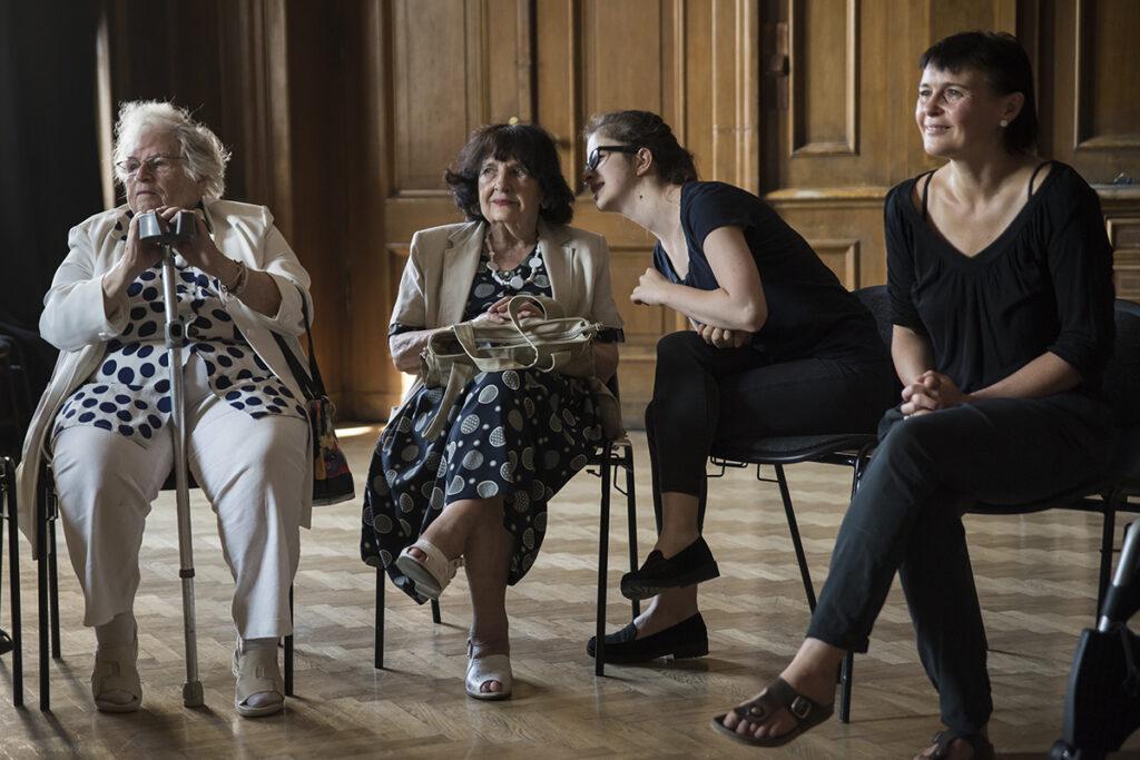 Cztery kobiety – dwie starsze i dwie młodsze – siedzą na krzesłach ustawionych w zabytkowej, drewnianej sali w Centrum Kultury ZAMEK. Spoglądają lekko w naszą lewą stronę. Młodsza, ubrana na czarno dziewczyna, pochyla się do czarnowłosej seniorki – szepce jej coś do ucha. Uczestniczki warsztatu są gustownie, elegancko ubrane. Druga seniorka trzyma przed sobą jedną kulę ortopedyczną.