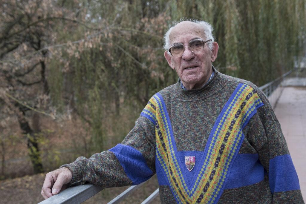 Starszy mężczyzna ubrany w szaro-niebieski sweter we wzory stoi na zewnątrz. Jest prawdopodobnie w parku lub ogrodzie. Za jego plecami rosną drzewa. Wśród pochylających się koron jest także wierzba. Pan Kazimierz ma założone przyciemniane okulary. Jego prawa ręka położona jest na balustradzie, o którą się lekko opiera.