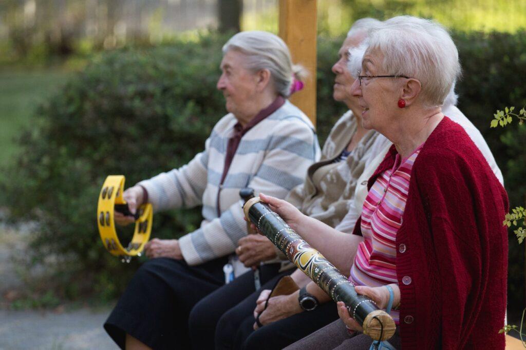 Cztery starsze mieszkanki Domu Pomocy Społecznej siedzą na ławce. Uwieczniono je z profilu. Z zainteresowaniem spoglądają prawdopodobnie w stronę grającej na gitarze artystki. Panie trzymają w dłoniach różne instrumenty muzyczne. Wspólnie grają i śpiewają. Kobieta najbliżej nas ubrana jest w wiśniowy sweterek. Na uszach ma utrzymane w podobnej barwie klipsy. Na nosie ma założone okulary. Zaaferowana koncertem lekko się uśmiecha.
