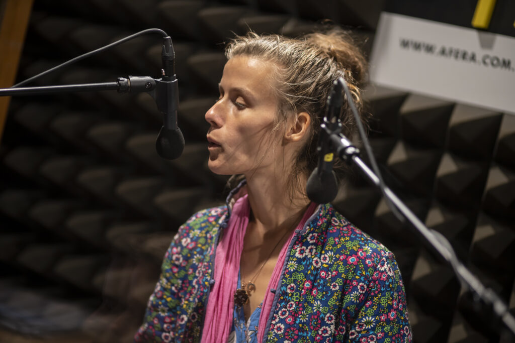Młoda kobieta, uwieczniona od piersi do czubka głowy stoi blisko mikrofonu. Głowę ma lekko odwróconą w swoją prawą stronę. Grymas na twarzy i ustawienie ust wskazują, że kobieta gwiżdże. Skierowana jest ustami w stronę radiowego mikrofonu. Postać ubrana jest w wielokolorową, pstrokatą tkaninę.
