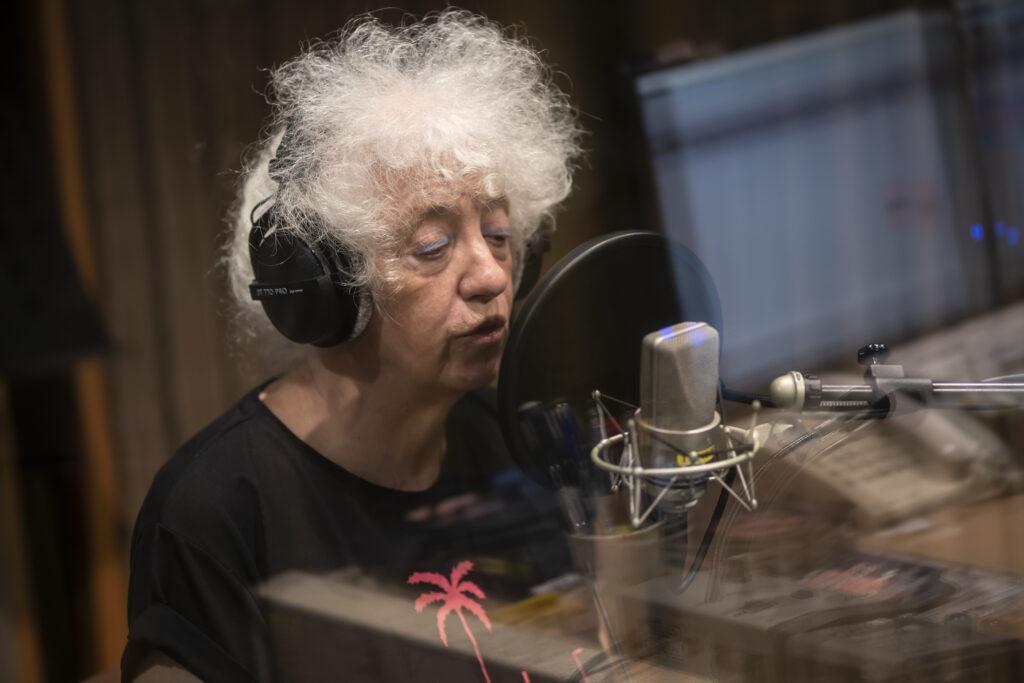Twarz starszej kobiety. Osoba ujęta na zdjęciu jest w trakcie wypowiadania jakichś słów do mikrofonu. To Pani Izabela Gustowska – artystka. Ubrana jest w czarny t-shirt z różowym nadrukiem w kształcie palmy. Na głowie ma burzę białych, kręconych włosów. Na twarzy delikatny makijaż.