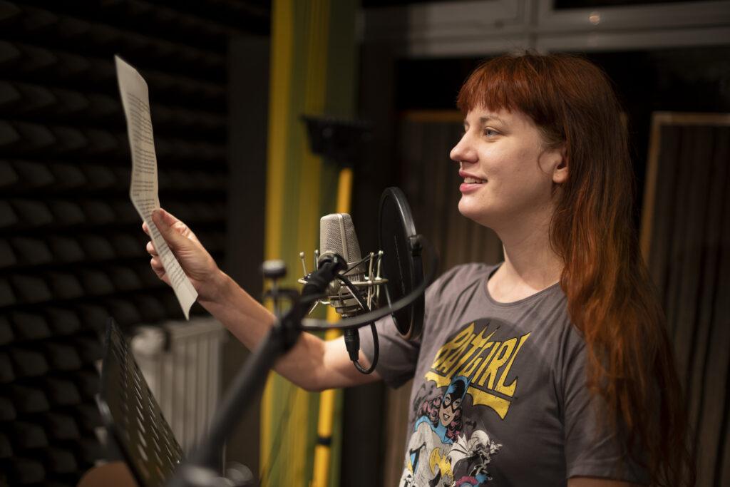 Młoda, uśmiechnięta, rudowłosa dziewczyna stoi do nas bokiem. Jest wyprostowana. W prawej ręce – uniesionej do góry – trzyma kartkę z tekstem, który prawdopodobnie czyta. Ubrana jest w brązowy t-shirt z komiksowym, kolorowym nadrukiem. Przed ustami radiowym mikrofon z osłonką.