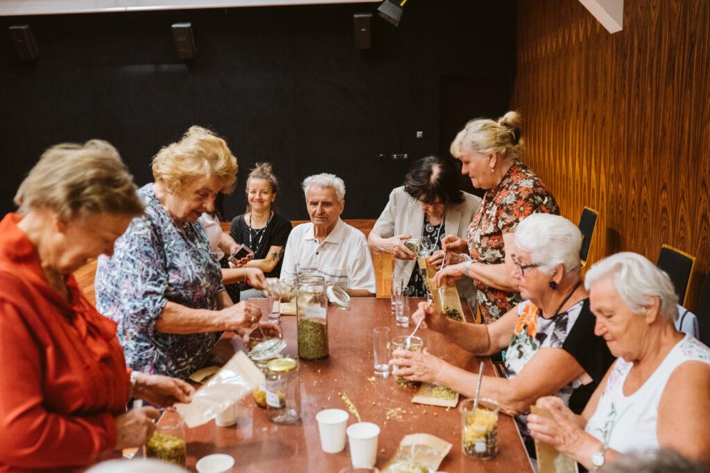 Dziewięcioosobowa grupa – w większości seniorek – siedzi lub stoi przy warsztatowym stole. Panie w skupieniu tworzą ziołowe herbatki. Dodają składniki do specjalnych saszetek. Całemu zdarzeniu przygląda się młodsza wolontariuszka. Szeroko uśmiecha się do fotografa.