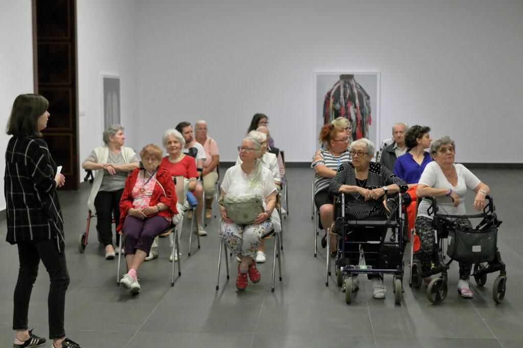 Kilkunastoosobowa grupa seniorek i seniorów – wśród nich pojedyncze głowy młodszych osób – siedzi na krzesłach w Sali Wystaw w Centrum Kultury ZAMEK. Przed nimi stoi kobieta ubrana w ciemnych kolorach – widzimy ją z profilu. To kuratorka wystawy zdjęć Pawła Bownika, o której właśnie opowiada. Część osób rozgląda się po ścianach, na których wiszą wielkoformatowe fotografie, inni wsłuchują się w opowieść kuratorki.