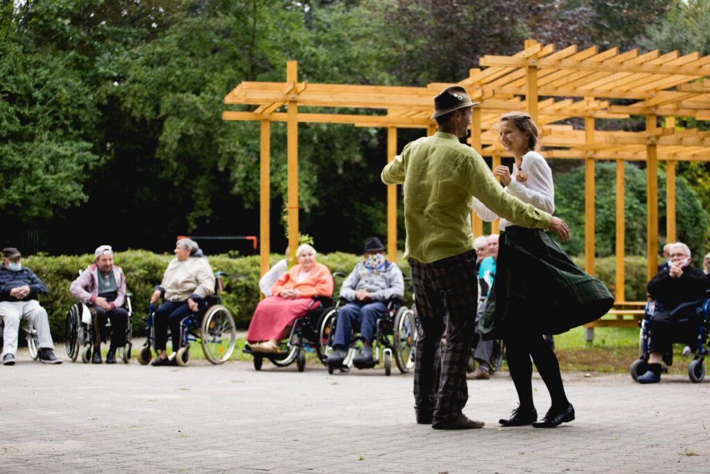 Na pierwszym planie para młodych tancerzy – chłopak i dziewczyna – prezentują tradycyjne wielkopolskie tańce grupie zgromadzonych seniorów. To mieszkańcy i mieszkanki jednego z poznańskich DPS-ów. Publiczność siedzi w oddali. Niektórzy klaszczą. Cała sytuacja ma miejsce w zielonym ogrodzie na Ugorach.