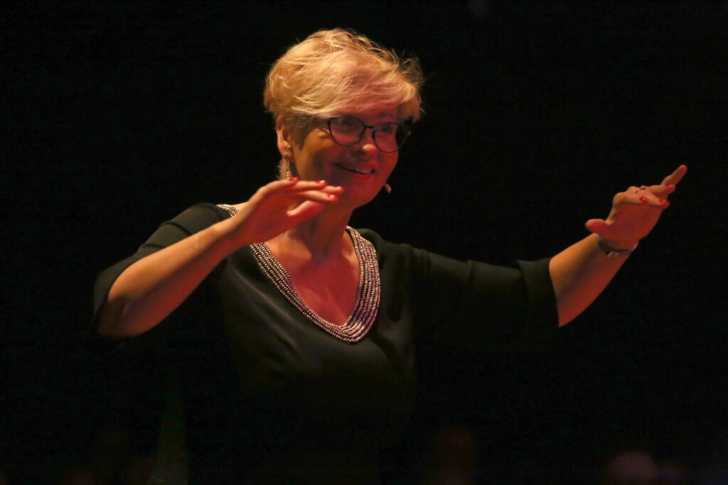 Zdjęcie przedstawia dyrygującą kobietę w czarnej sukni i okularach z uniesionymi rękoma. Jej mina wyraża radość i skupienie.