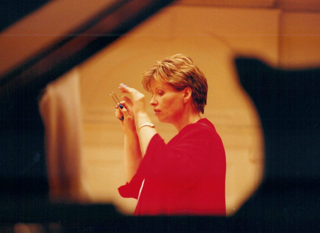 W centralnym punkcie fotografii zrobionej zza fortepianu znajduje się kobieta w czerwonym kostiumie. W skupieniu spogląda na niewidoczne w kadrze nuty. Dyryguje. Obie ręce ma uniesione, a w prawej dłoni dzierży kamerton.