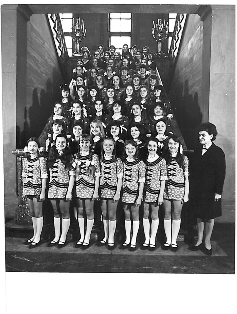 Czarno-białe zdjęcie przedstawia kilkadziesiąt dziewcząt z Chóru Dziewczęcego Skowronki. Dziewczęta stoją na zabytkowych schodach w Centrum Kultury ZAMEK, ubrane w białe podkolanówki i ozdobne sukienki typu mini. Wraz z nimi, w pierwszym rzędzie stoi dyrygentka.