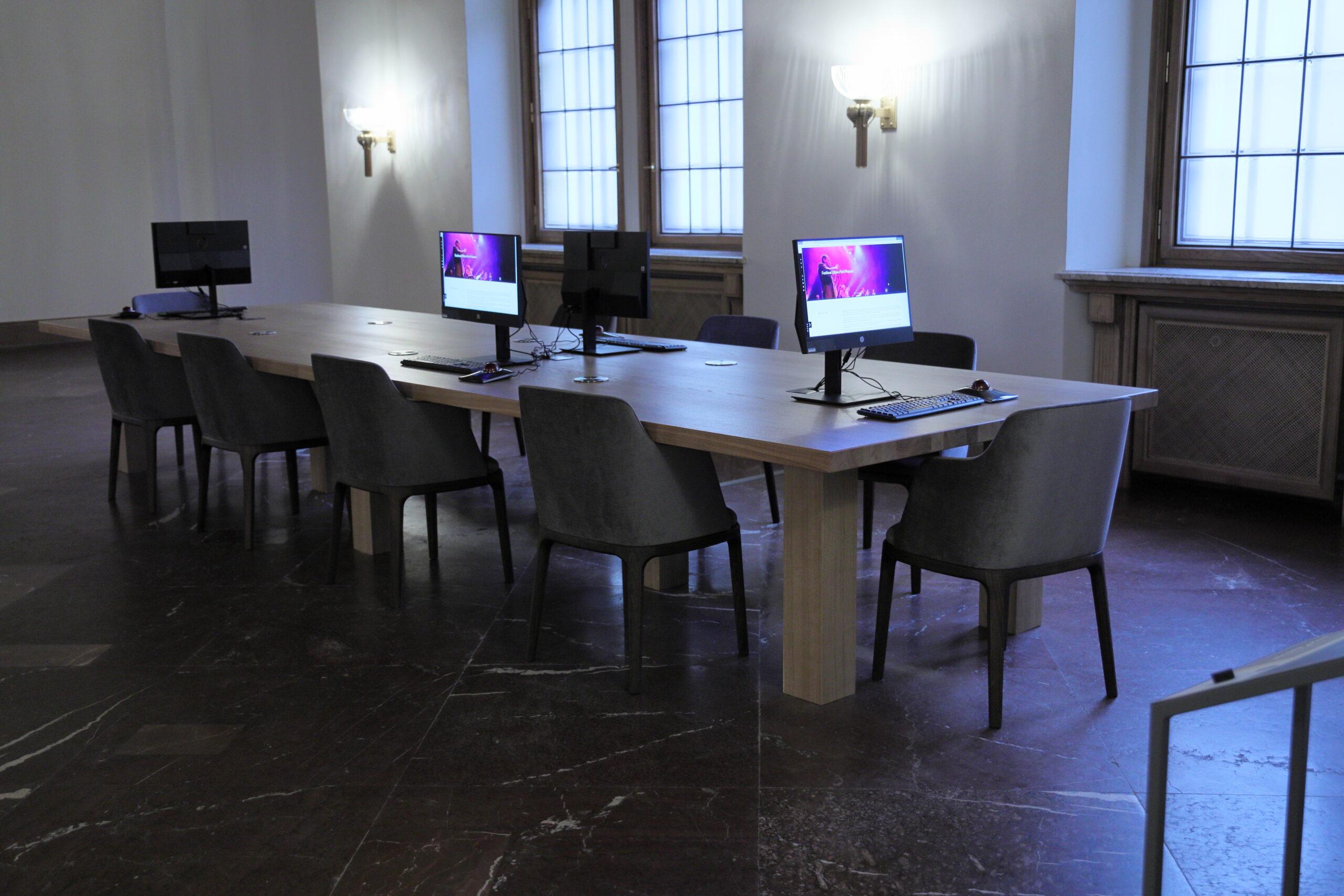 Widok pomieszczenia mediateki: na marmurowej podłodze stoi duży, jasny stół otoczony szarymi krzesłami. Na stole widać cztery monitory, z których dwa są włączone i mają kolorowe ekrany. Za stołem widać ścianę z lampami - kinkietami, z których pada światło, oraz z oknami.