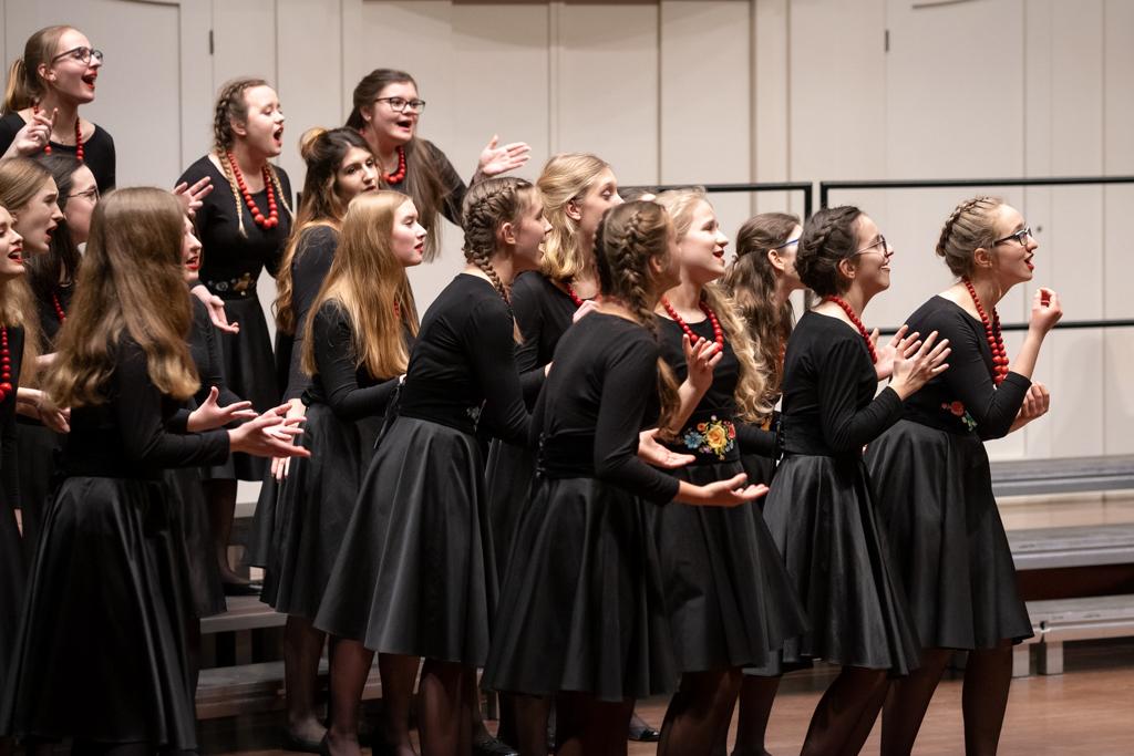 Ujęcie z boku sceny przedstawia grupę dziewcząt w czarnych strojach i czerwonych koralach śpiewa, zwracając się ku publiczności. Chórzystki są ukazane w ruchu i żywo gestykulują.