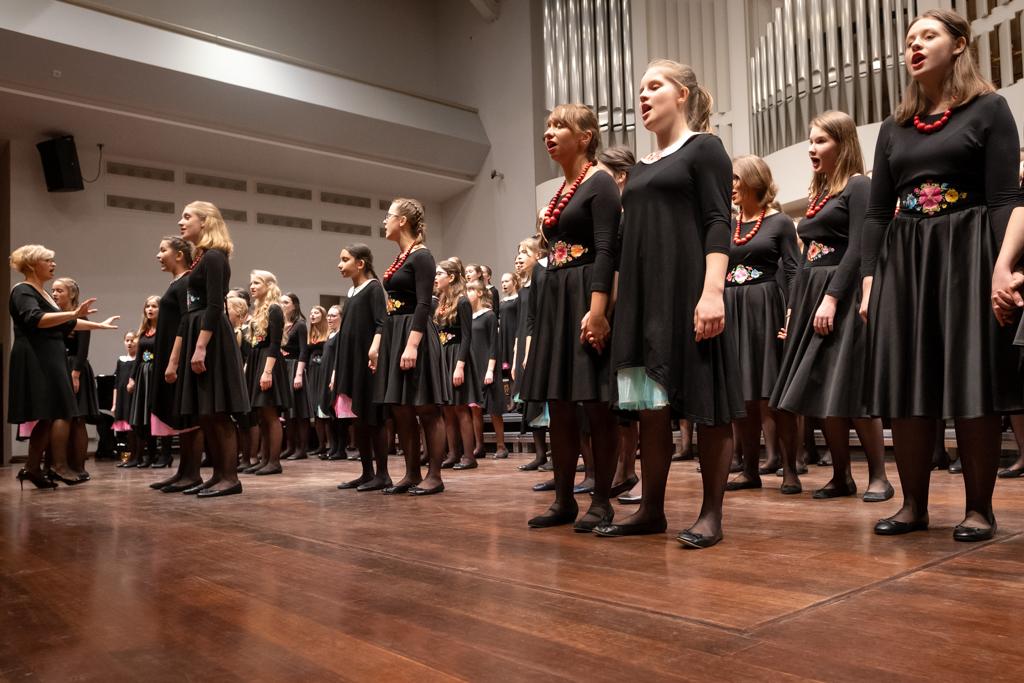 Na scenie Auli Nova w Poznaniu występuje chór dziewczęcy. Chórzystki ubrane są w czarne kostiumy, a na szyjach mają zawieszone czerwone korale. Przed chórem stoi dyrygentka, również w czarnym kostiumie.